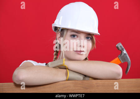 Portrait of a construction worker holding a hammer - Stock Photo