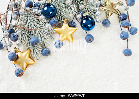 Christmas background border with corner composition made of green Xmas fir branch, blue berries and gold New Year decoration - Stock Photo