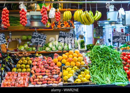 Greengrocer at the famous public market Mercat de Sant Josep de la Boqueria Barcelona - Stock Photo