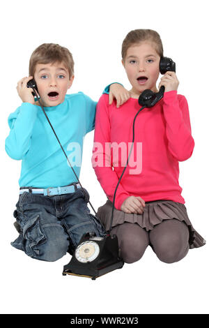 Shocked children using the telephone - Stock Photo