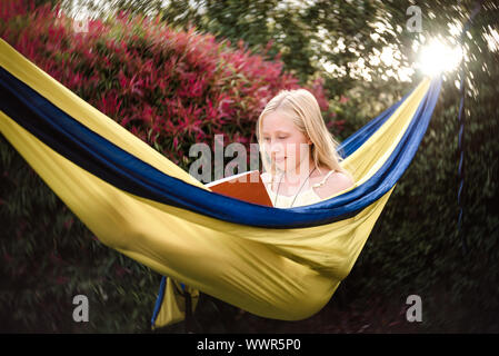 Adolescent girl reading in a yellow hammock