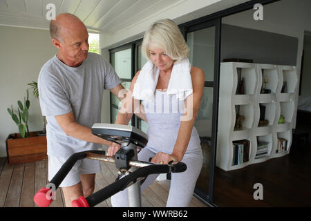 Man helping his wife use an exercise machine - Stock Photo
