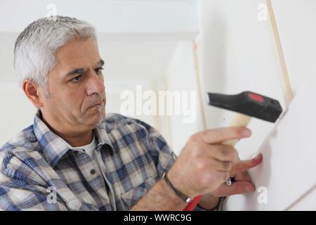 Grey-haired man repairing house - Stock Photo