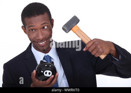 Man trying to break into a piggy bank with a hammer - Stock Photo
