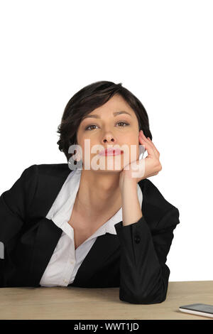 Attractive businesswoman sitting at her desk - Stock Photo