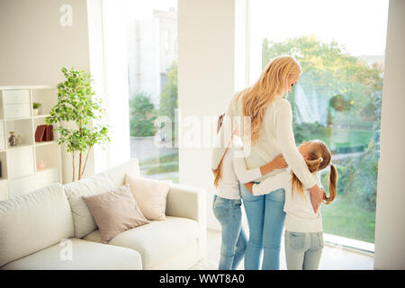 Rear back behind view of nice stylish trendy slim people kind tender mom mommy mum girls hugging in front of window in modern light white interior - Stock Photo