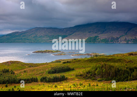 Idyllic landscape of Scotland, UK.Moody sky with dark clouds above mountain range and sunshine over lake with small islands.Typical Scottish weather. - Stock Photo
