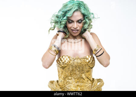 Latin woman dancing, gold dress and jewels. Young woman with her short green emerald hair - Stock Photo