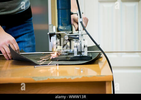 Worker man cutting a metal pipe in two pieces close-up. - Stock Photo