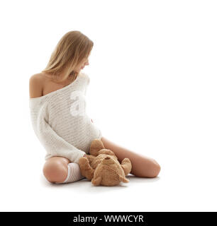 picture of lovely blond in white sweater with teddy bear - Stock Photo