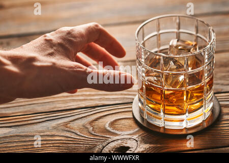 Man's hand reaching to glass of whiskey with ice cubes. Alcoholism concept. - Stock Photo