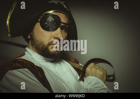 Sailor, Man with beard dressed like a pirate, with eye patch and steel sword - Stock Photo