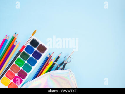 Colorful pencils, watercolors, holographic pencil box on blue background with copyspace. Flat lay style. Back to school concept. - Stock Photo