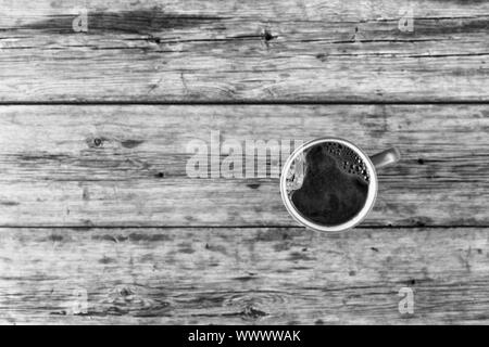 The blurred background, blur. A cup of black coffee on a wooden table. View from above. - Stock Photo