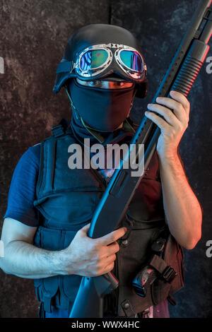 Terrorism, man armed with balaclava and bulletproof vest, gun and shotgun, kalashnikov - Stock Photo