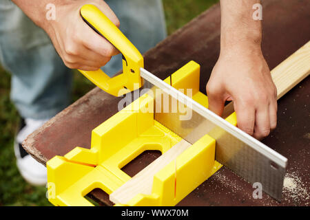 Man cutting a slat of wood using a saw and miter box outdoors. - Stock Photo