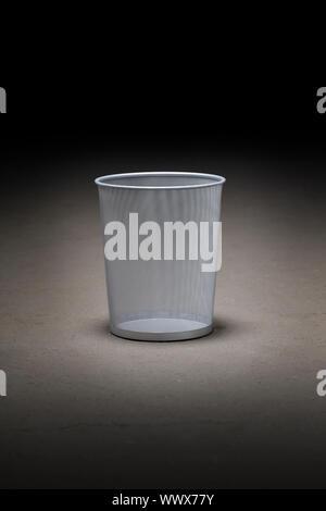 Empty wastepaper basket on dirty concrete floor. - Stock Photo