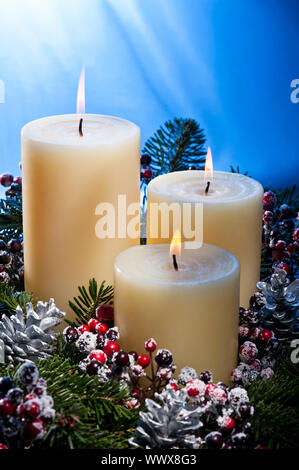 Three candles in an advent flower arrangement - Stock Photo