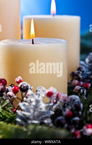 Three burning candles in an advent flower arrangement - Stock Photo
