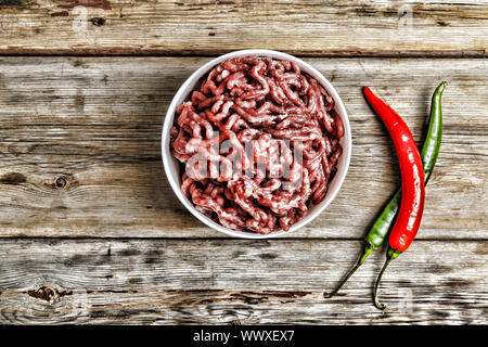 Raw Meat stuffing in a white bowl on a wooden table, rural style. top view - Stock Photo