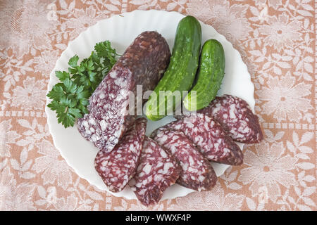 Slices of sausage and cucumber on the plate. - Stock Photo