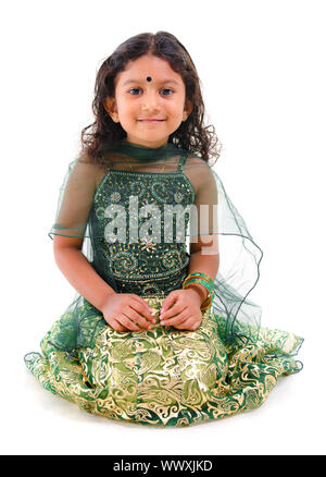 Young little Asian Indian girl smiling and sitting on white background - Stock Photo