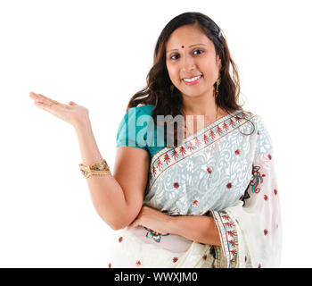 Cheerful traditional Asian Indian woman arm out showing empty space, isolated on white - Stock Photo