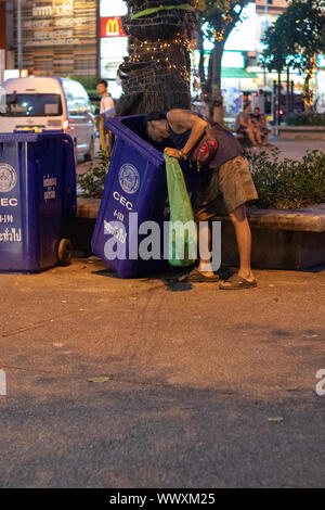 Homeless man looking for plastic waste for recycling  in Chiangmai Thailand. - Stock Photo