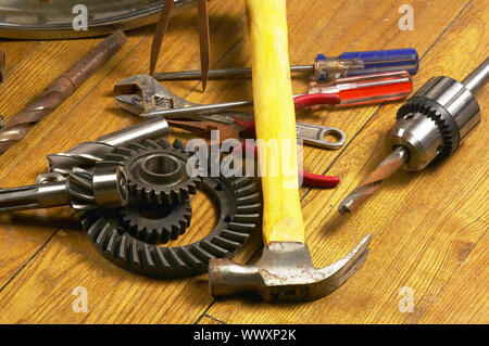 bounch of rusty tools and gears on the wood floor - Stock Photo