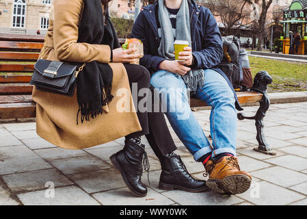 crop image. couple sitting on bench eating fast food drinking tea - Stock Photo