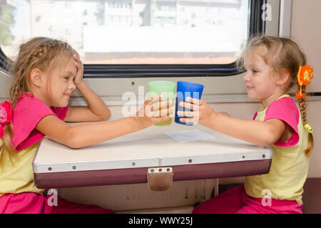 Two little sisters in identical pajamas drinking tea in the train at the table on outboard second-class carriage - Stock Photo