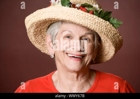 Senior woman in a red shirt and straw hat - Stock Photo