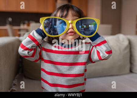 Cute little girl playing with oversized novelty sunglasses at home