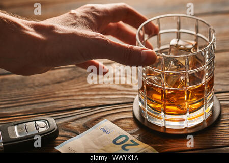 Man's hand reaching to glass with alcohol drink and car key. Drink and drive concept. - Stock Photo
