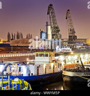 freight ships and cranes in inland port Duisburg at night, Duisburg, Ruhr Area, Germany, Europe - Stock Photo