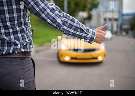 Photo of man with outstretched hand stopping taxi in afternoon on blurred background of modern city - Stock Photo