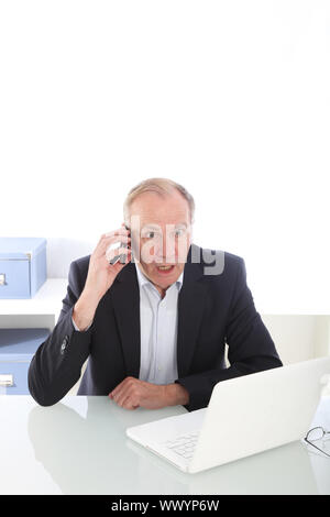 Middle-aged businessman seated at his desk reacting to news received over his mobile phone in disbelief - Stock Photo