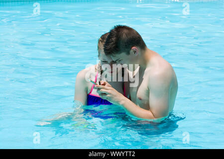 Teenage girl and boy watching pictures on smartphone taken during photo shoot in luxury hotel swimming pool. Summer vacation concept - Stock Photo