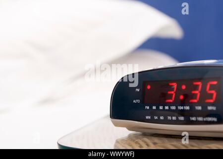 Empty bedroom with focus on alarm clock - Stock Photo