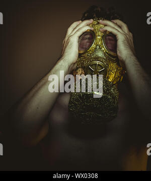 Man with gold gas mask and arabesques in poses of drowning and desperation, depression and psychiatry concept. - Stock Photo