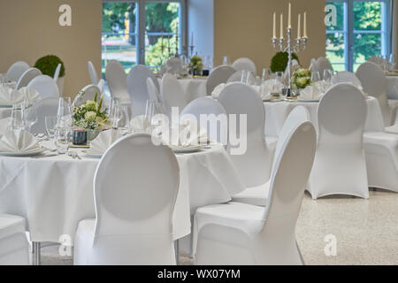 Room with festively bright tables covered in white - Stock Photo