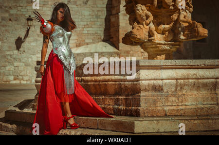 Medieval, Beautiful brunette woman wearing gold and copper corset in goddess and warrior poses. fantasy and imagination concept Stock Photo