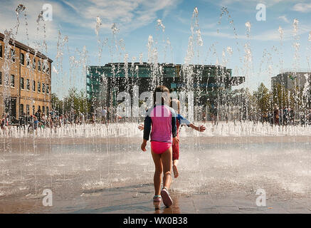 Children at play in the fountains in Granery Sq Kings Cross London UK - Stock Photo