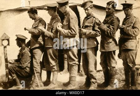 """British soldiers synchronising their watches on the front line, First World War, 1914-1918, (1933). 'Punctuality was no longer the """"Courtesy of Kings"""" in Edward VII's phrase, but the """"Safety of Soldiers""""...all camps had a post surmounted by a clock by which all troops regulated their watches. In France before an attack, watches were synchronised to obtain unanimity of movement and perfect co-operation at zero hour - the name given to the moment of attack.' From """"The Pageant of the Century"""". [Odhams Press Ltd, 1933] - Stock Photo"""