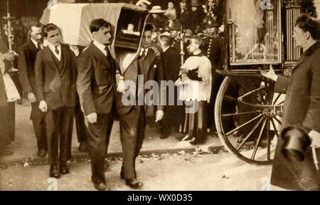 """Funeral of Terence MacSwiney, Cork, Ireland, 31 October 1920, (1933). The coffin, wrapped in Sinn Féin colours, is carried out of the Cathedral of St Mary and St Anne. MacSwiney (1879-1920), an Irish playwright, author and politician, was elected as Sinn Féin Lord Mayor of Cork during the Irish War of Independence in 1920. He was arrested by the British Government on charges of sedition and imprisoned in Brixton Prison. He died there on 25 October 1920 after 74 days on hunger strike. From """"The Pageant of the Century"""". [Odhams Press Ltd, 1933]"""