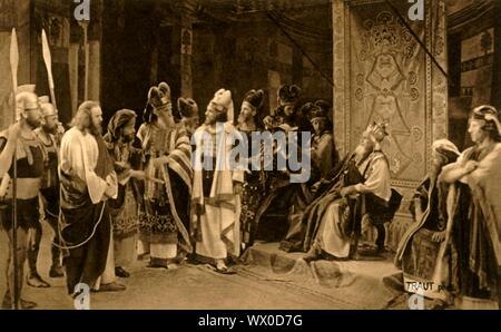 Jesus before Herod, 1922. Jesus (Anton Lang) appears before king Herod (Gregor Breitsamter) - also on stage are Sebastian Lang as the high priest Annas (or Ananias), and Hugo Rutz as high priest Joseph ben Caiaphas: players in the Oberammergau Passion Play. The play is performed every 10 years, on open-air stages, by the inhabitants of the village of Oberammergau in Bavaria, Germany. First staged in 1634, the play tells the story of Jesus' passion, culminating in his crucifixion. The event has become a tourist attraction, with audiences coming from all over the world. Official postcard of the - Stock Photo