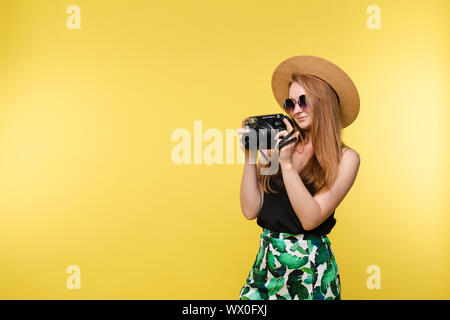 A girl in a hat and sunglasses with camera. - Stock Photo