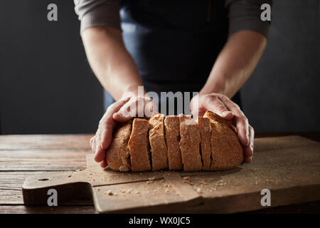 Fresh home slice bread in male's hands on the wooden board. - Stock Photo