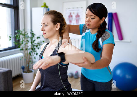 Chinese woman physiotherapy professional giving a treatment to an attractive blond client in a bright medical office - Stock Photo