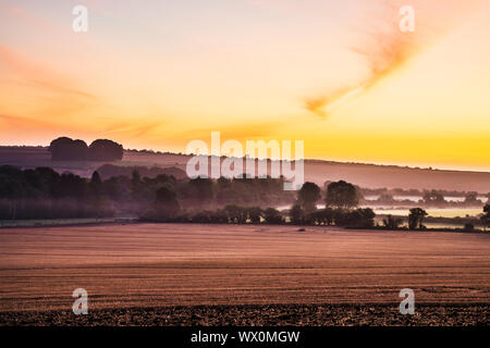 A late summer sunrise over the Marlborough Downs near West Kennet. - Stock Photo